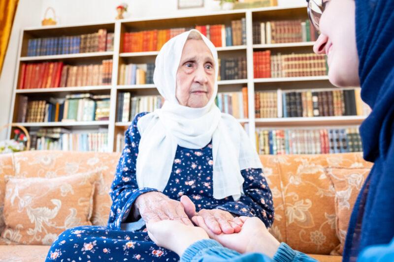 Happy arabic muslim granddaughter holding her grandmother hands